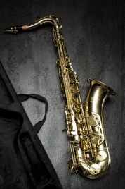 brass saxophone on gray table near black bag